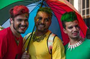 three man under multi coloured umbrella