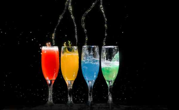 four champagne flutes with assorted color liquids