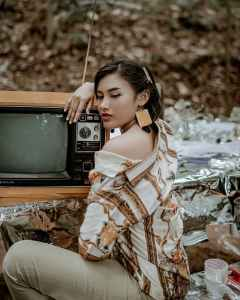 woman wearing white and brown shirt beside tv