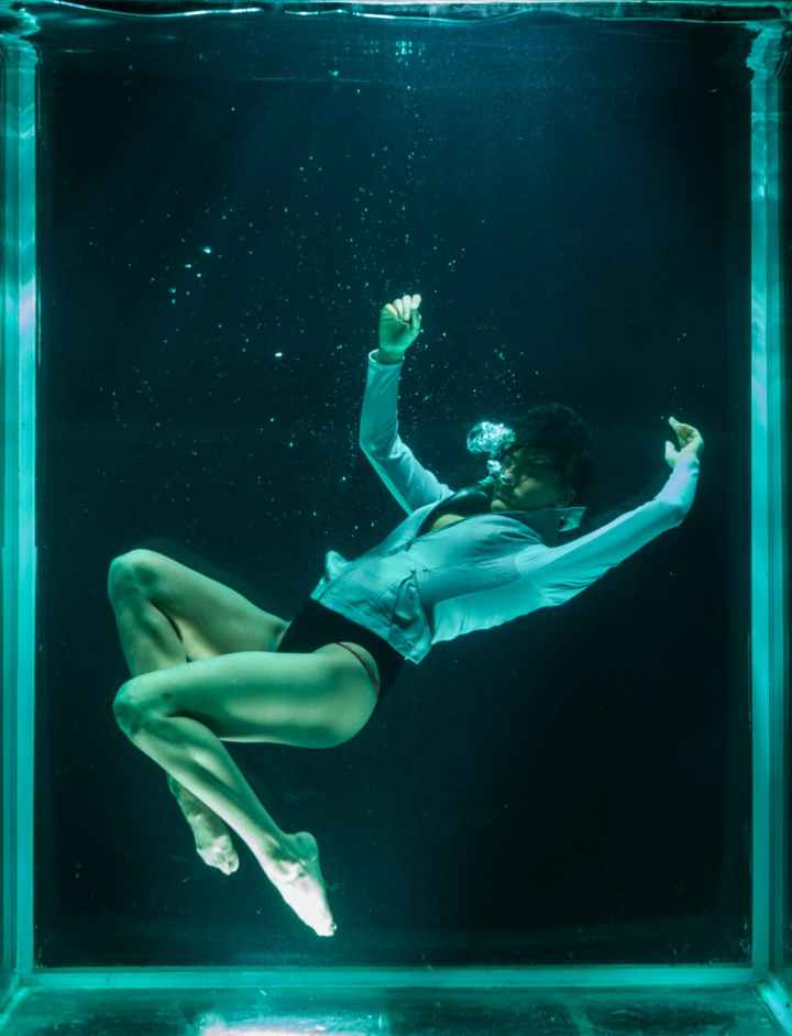 person wearing white long sleeved shirt in underwater